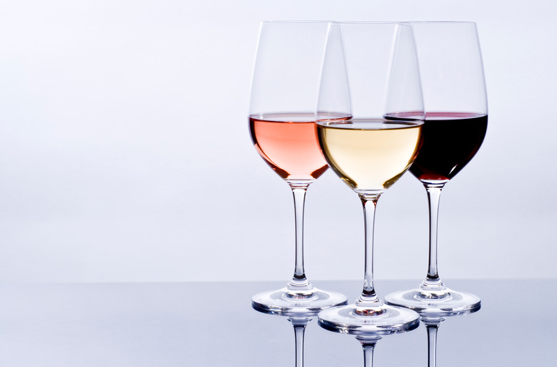 Three wine glasses filled with colourful wine