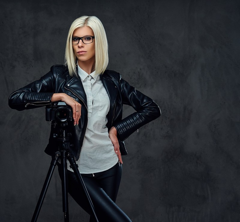 Blond photographer female on a grey background